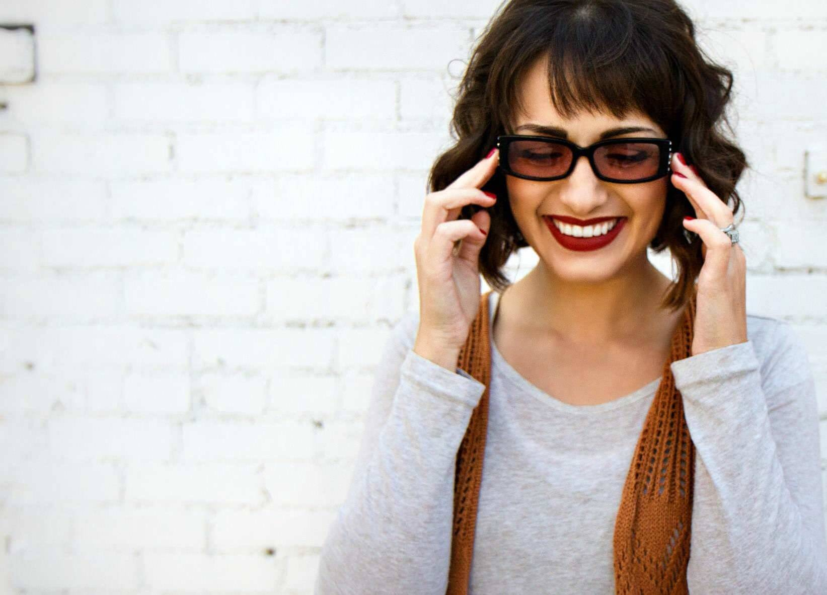 Woman wearing migraine glasses and smiling