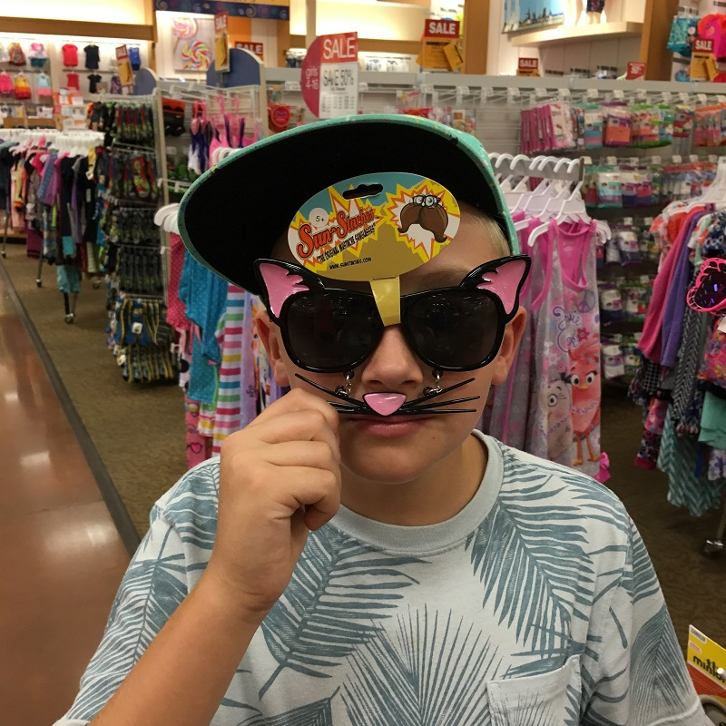 Boy wearing dark glasses in a big-box store