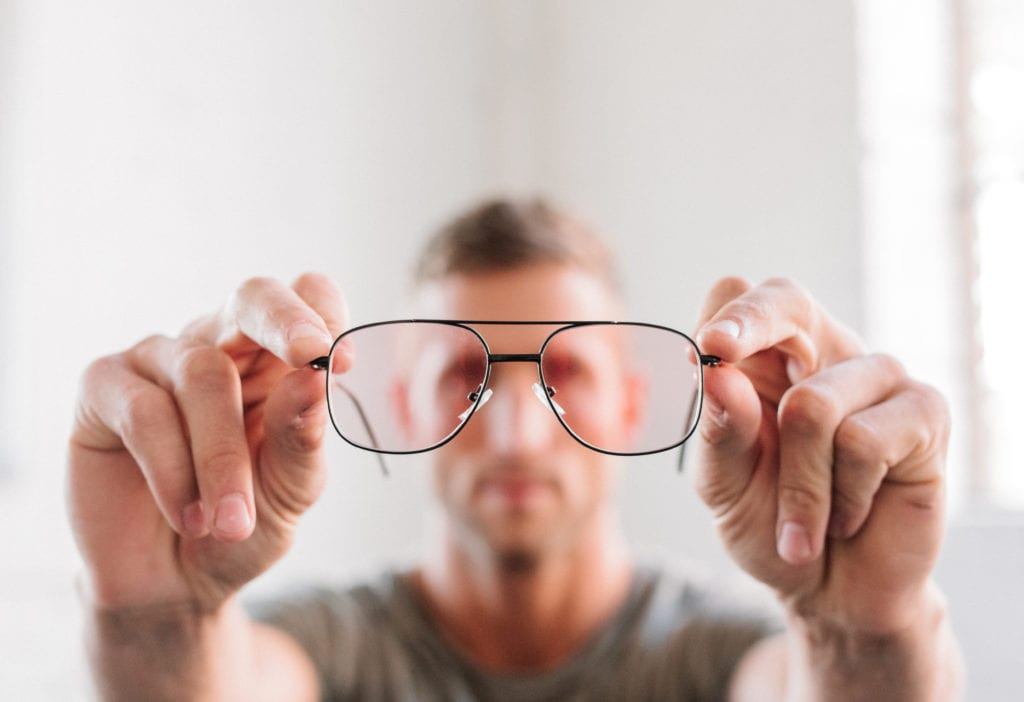 Man holding eyeglasses. Glasses can get scratched but replacing the lenses on glasses is pretty easy with Lens On Us.