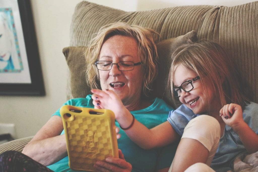 A woman and little girl reading and smiling. Living with migraine does not have to keep you away from the people you love.