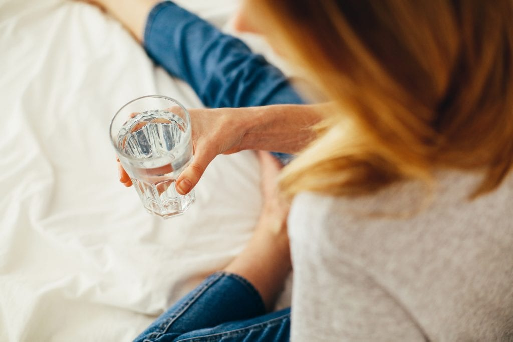 woman drinking glass of water during a migraine attack